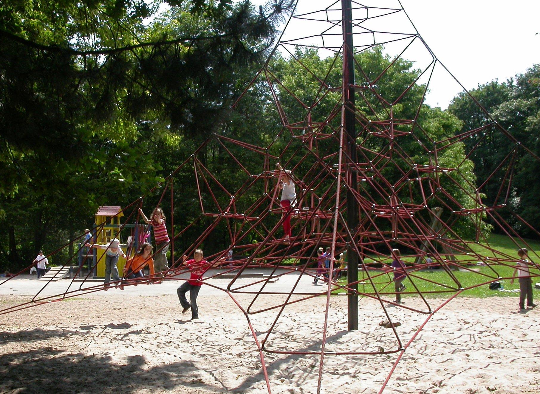 spielende Kinder auf der Kletterpyramide auf dem Spielplatz im Freizeitpark.