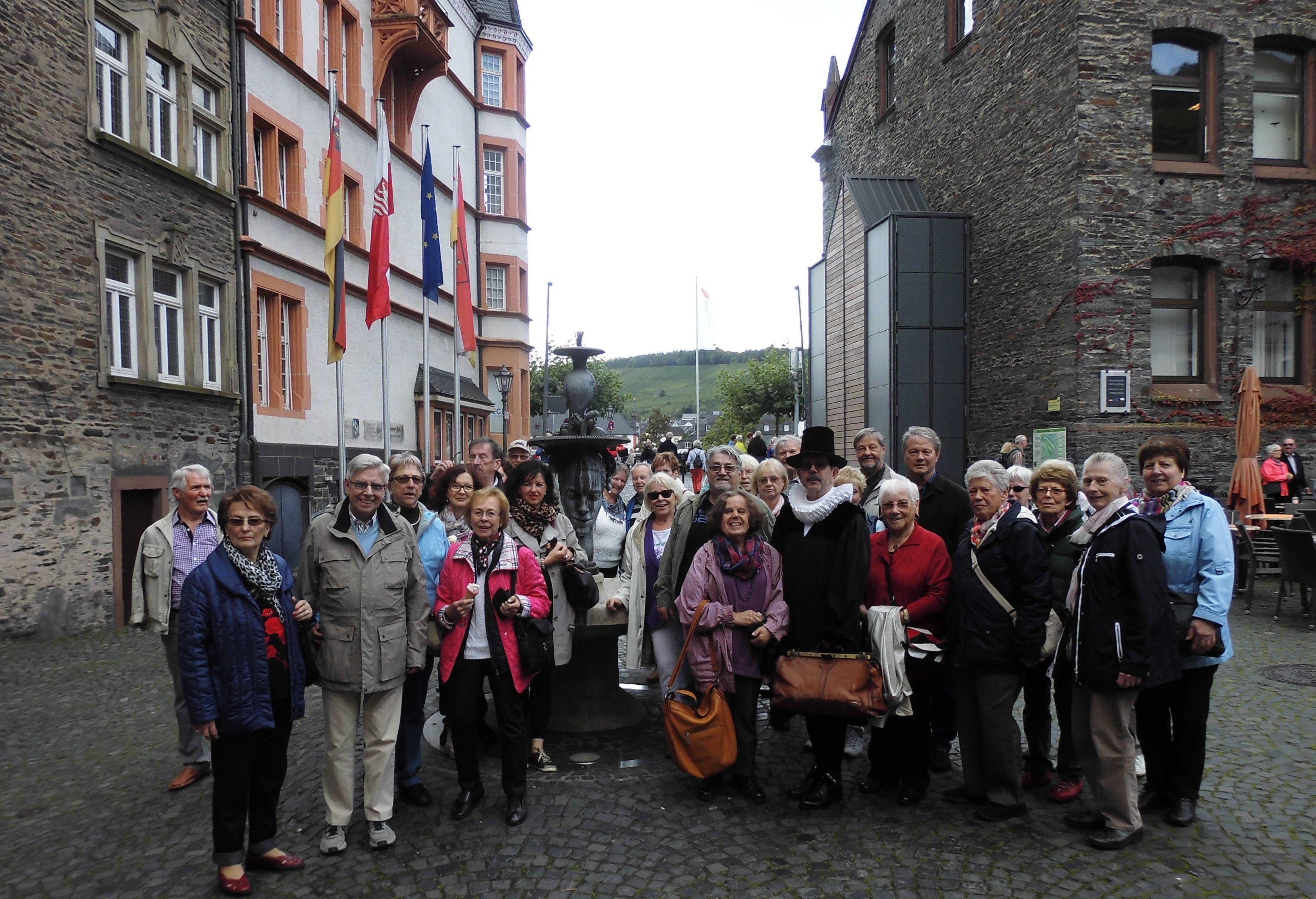 Gruppenbild einer Seniorengruppe bei einem Ausflug auf einem Platz einer Altstadt