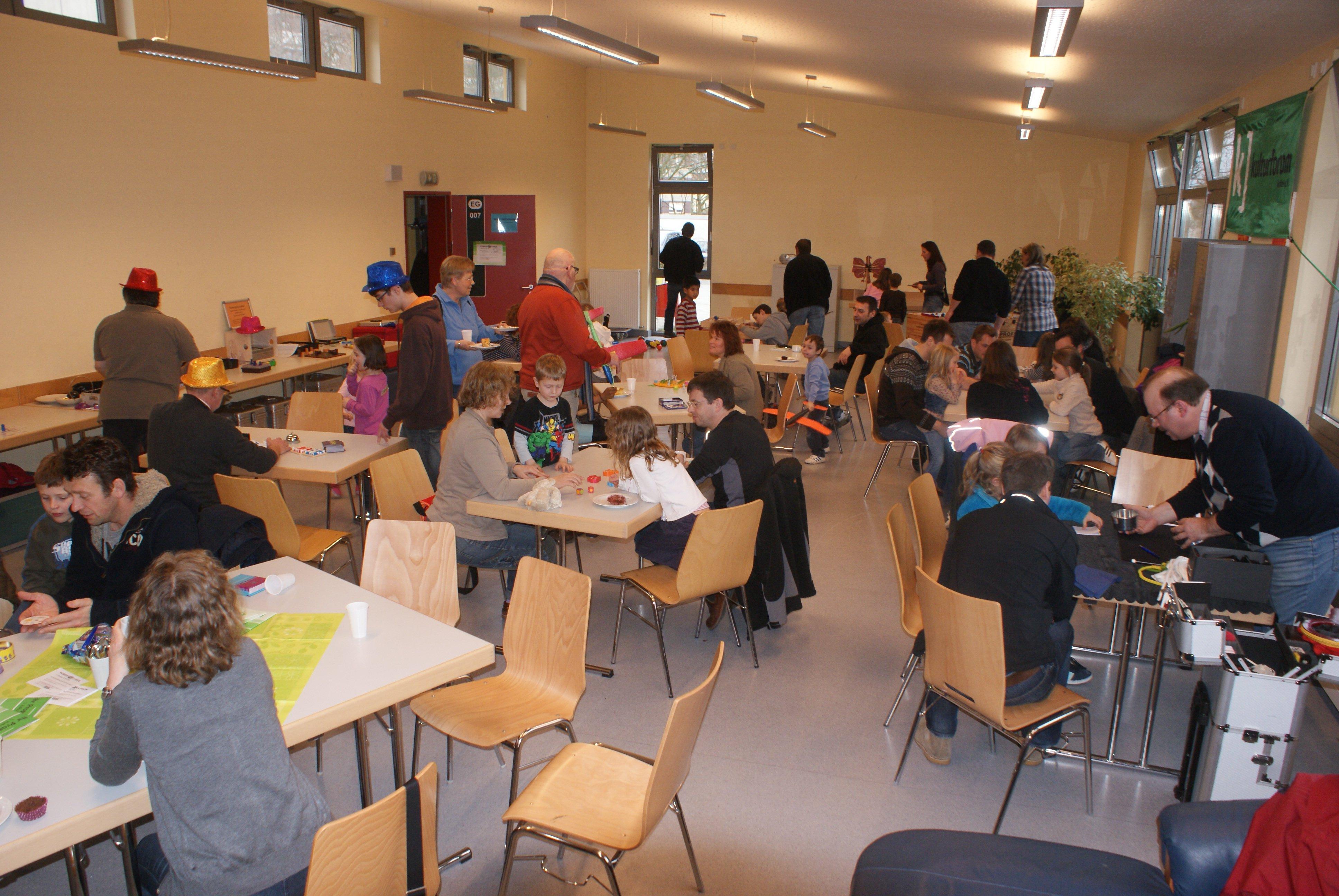Viele Tische mit Personengruppen bei Gesellschaftsspielen im Freizeithaus
