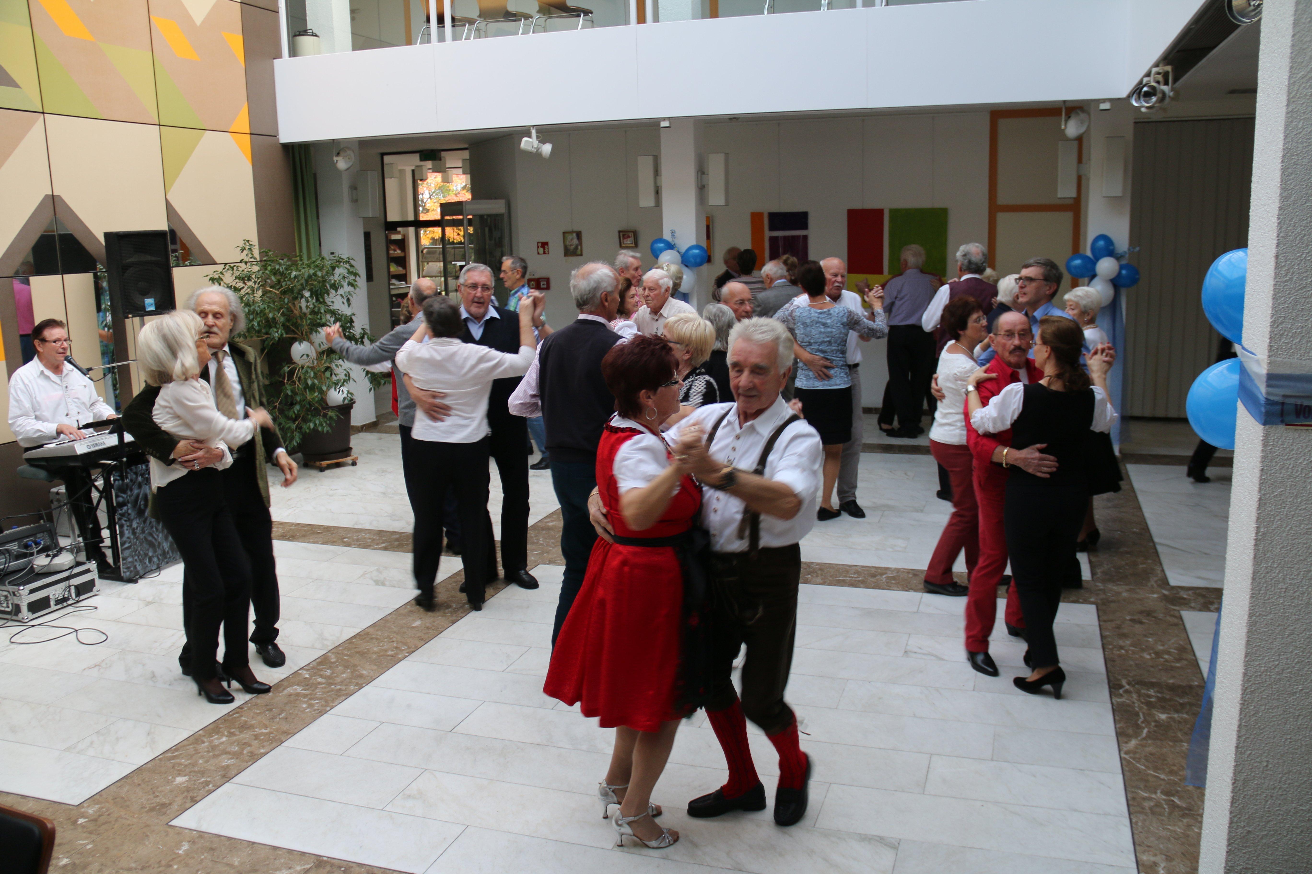 In Pärchen tanzende Senioren im Saal des Rathauses beim Tanztee