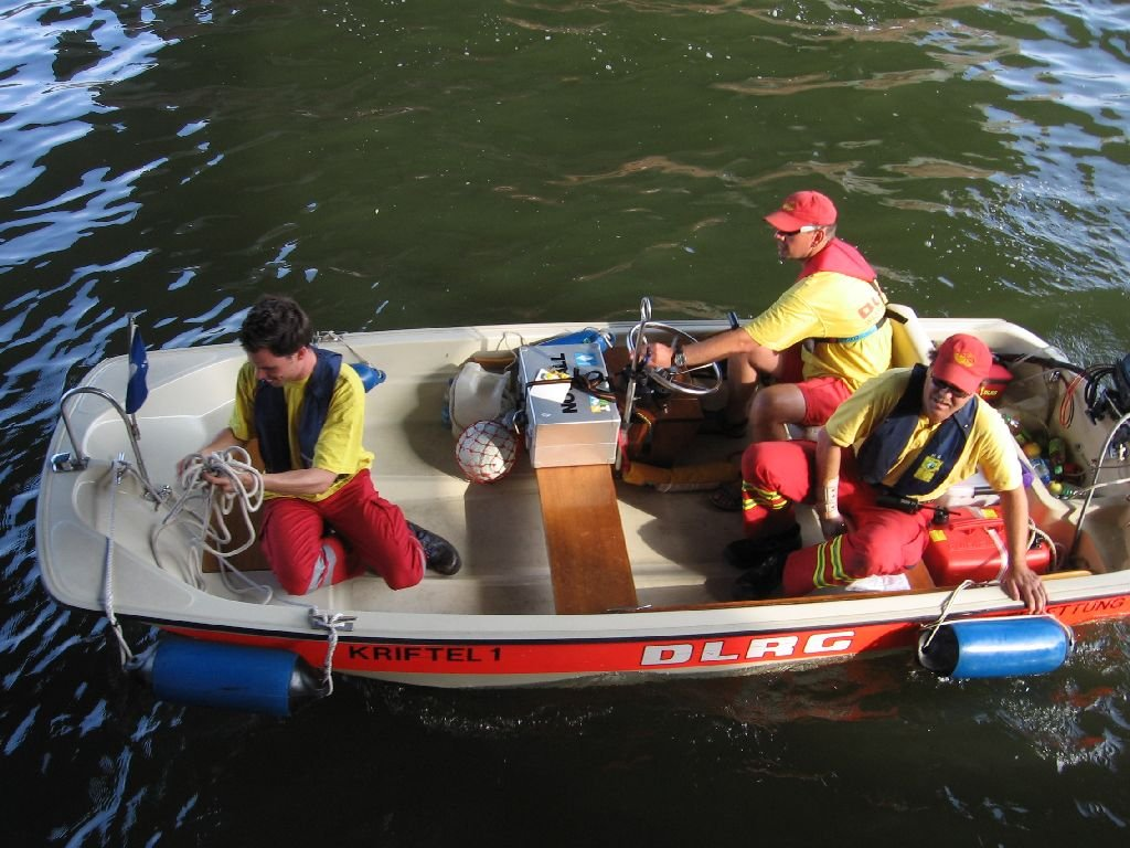 Aufsicht auf ein Rettungsboot mit drei Insassen in Kleidung der DLRG beim Anlegen an den Steg
