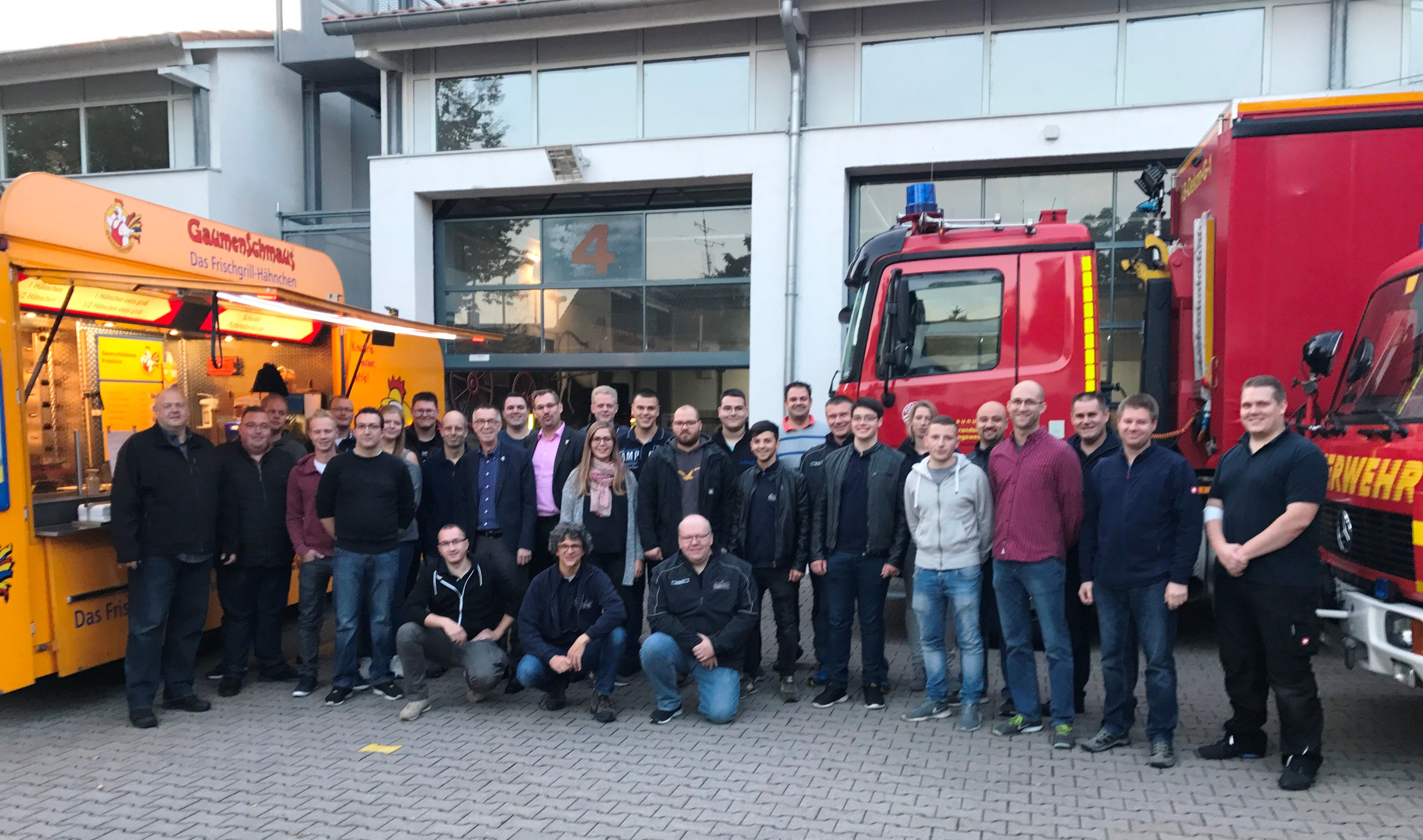 Ein Gruppenbild der Helfer der Freiwilligen Feuerwehr vor einem Imbisstand und einem Einsatzfahrzeug