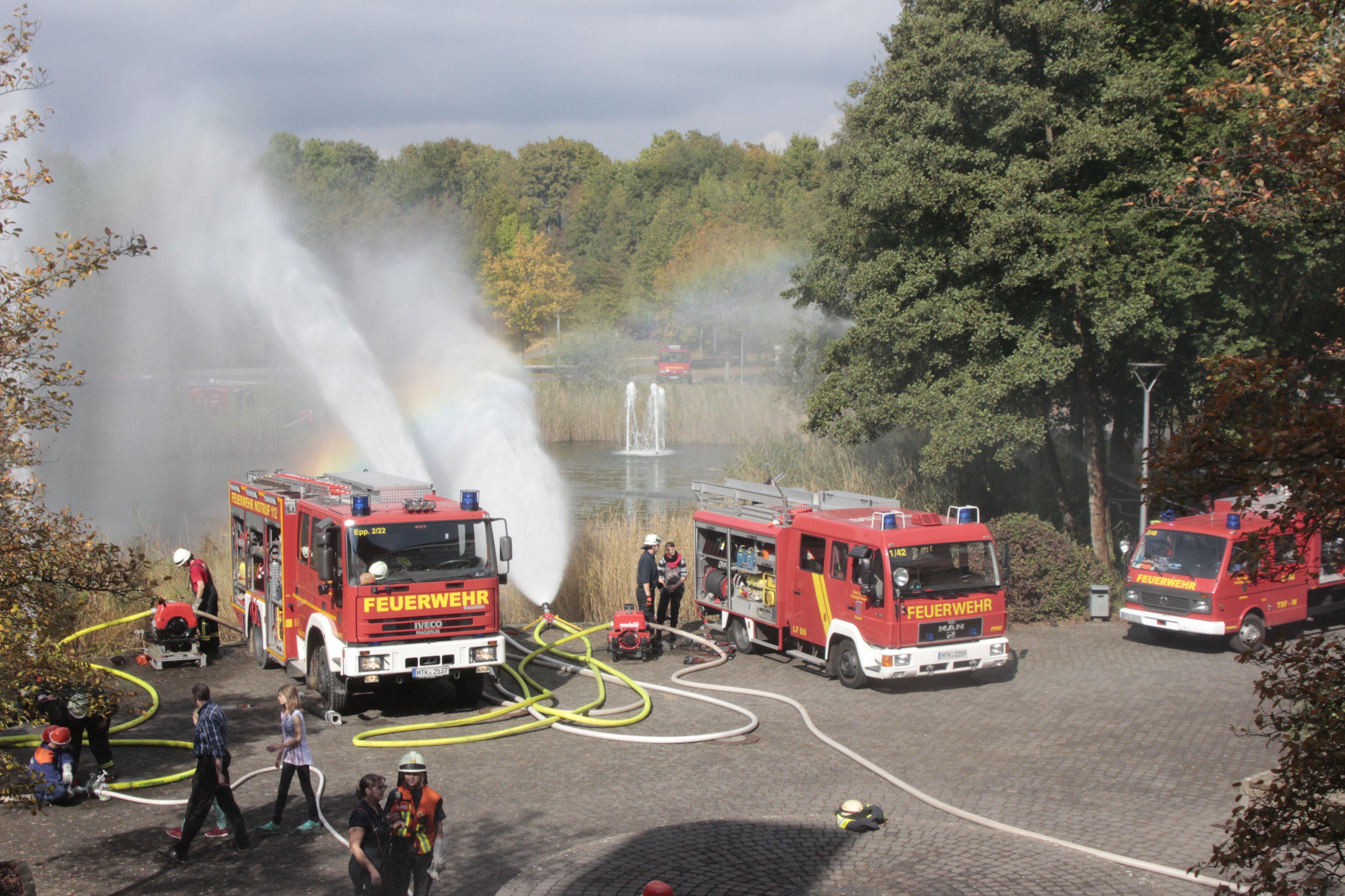 Mehrere Feuerwehrwagen mit Schläuchen, aus denen Wasser spritzt bei einer Löschübung mit der Jugendfeuerwehr