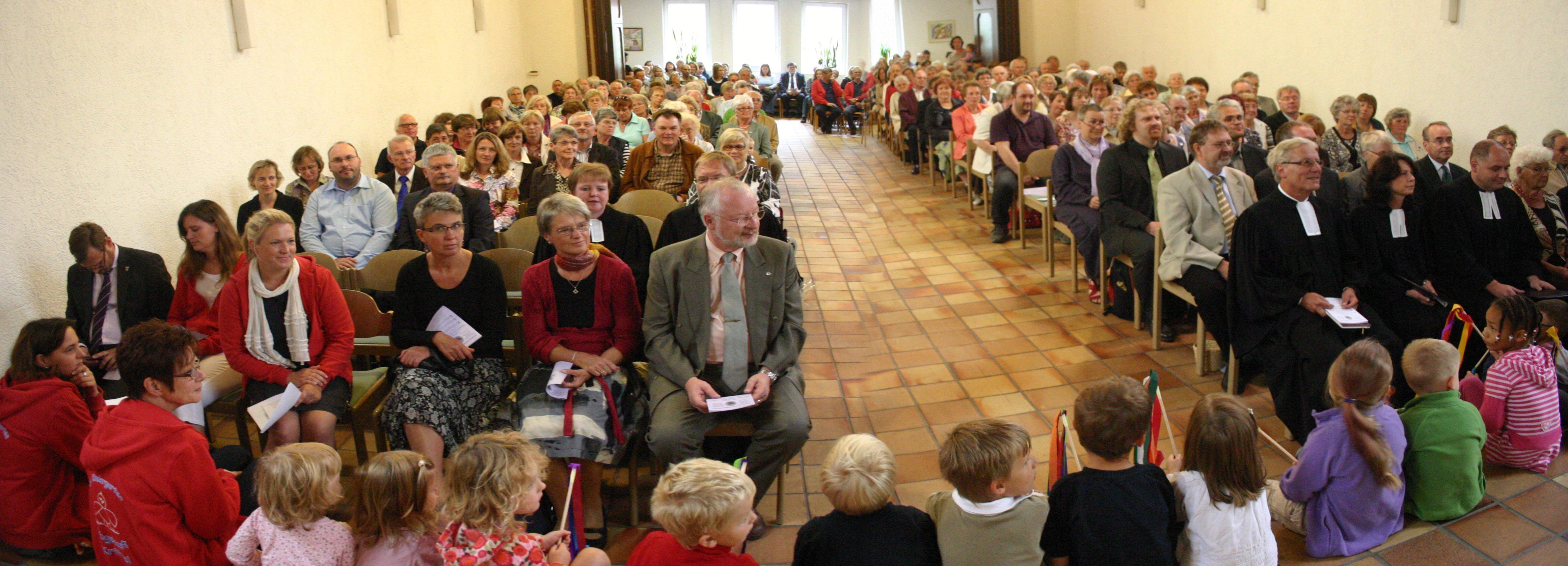 Ein vollbesetzter Kircheninnenraum bei einem Gottesdienst, auf den vorderen Stufen sitzen Kinder