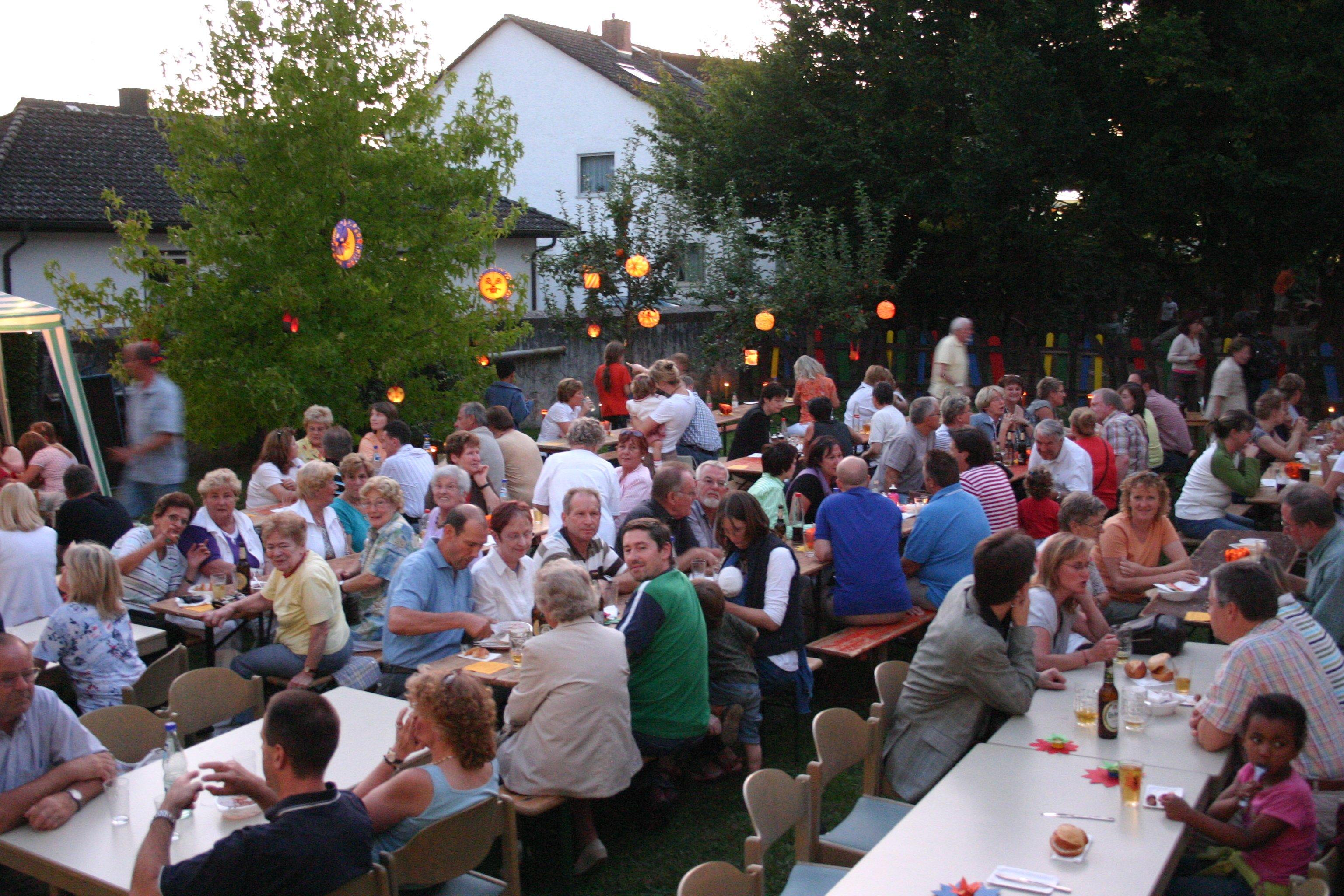 Viele Menschen auf Bierbänken im Kirchgarten beim Sommerfest, in den Bäumen hängen Lampions