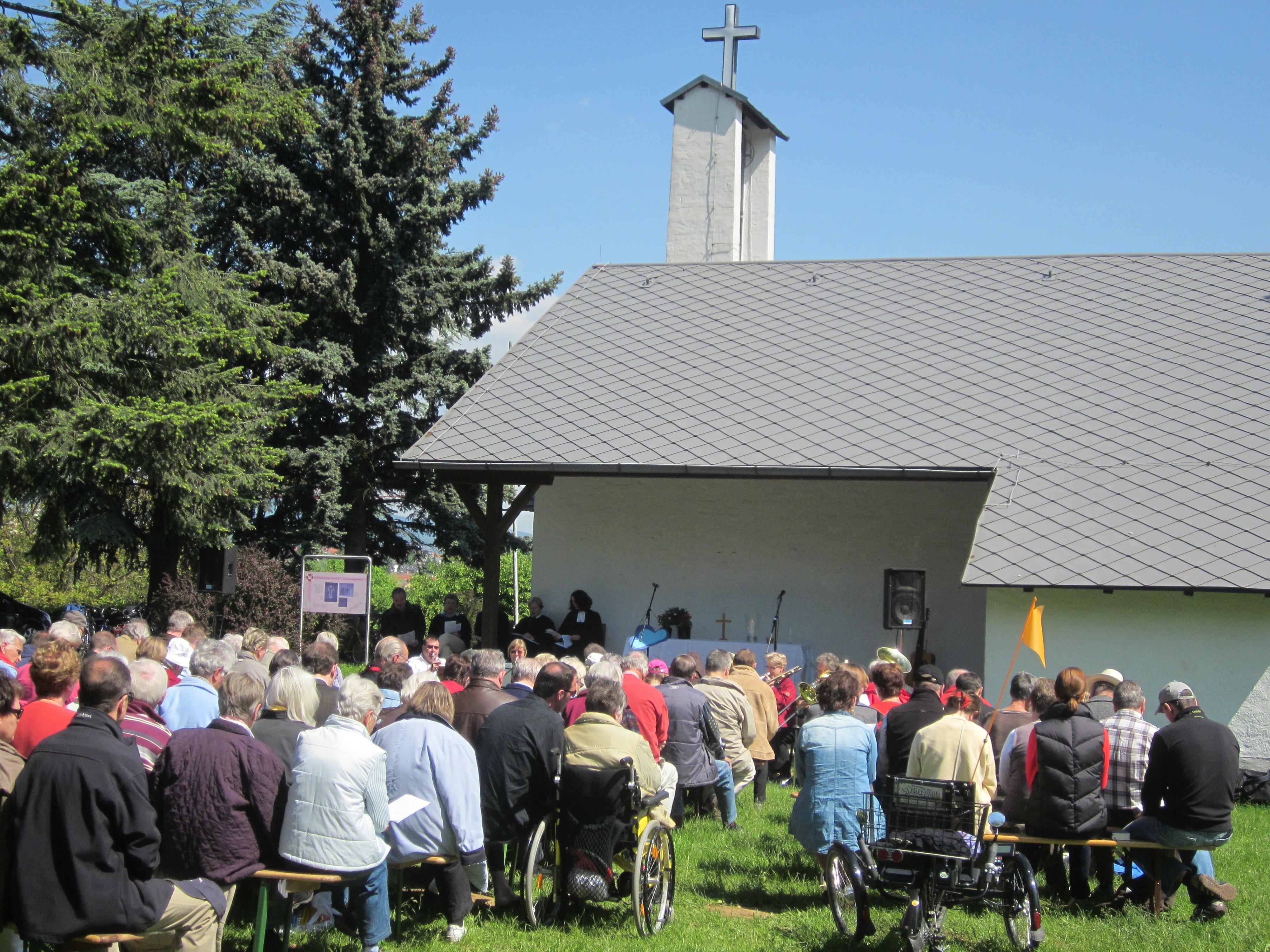 Gemeinde auf Bänken im Freien vor der Bonifatiuskapelle während eines Gottesdienstes