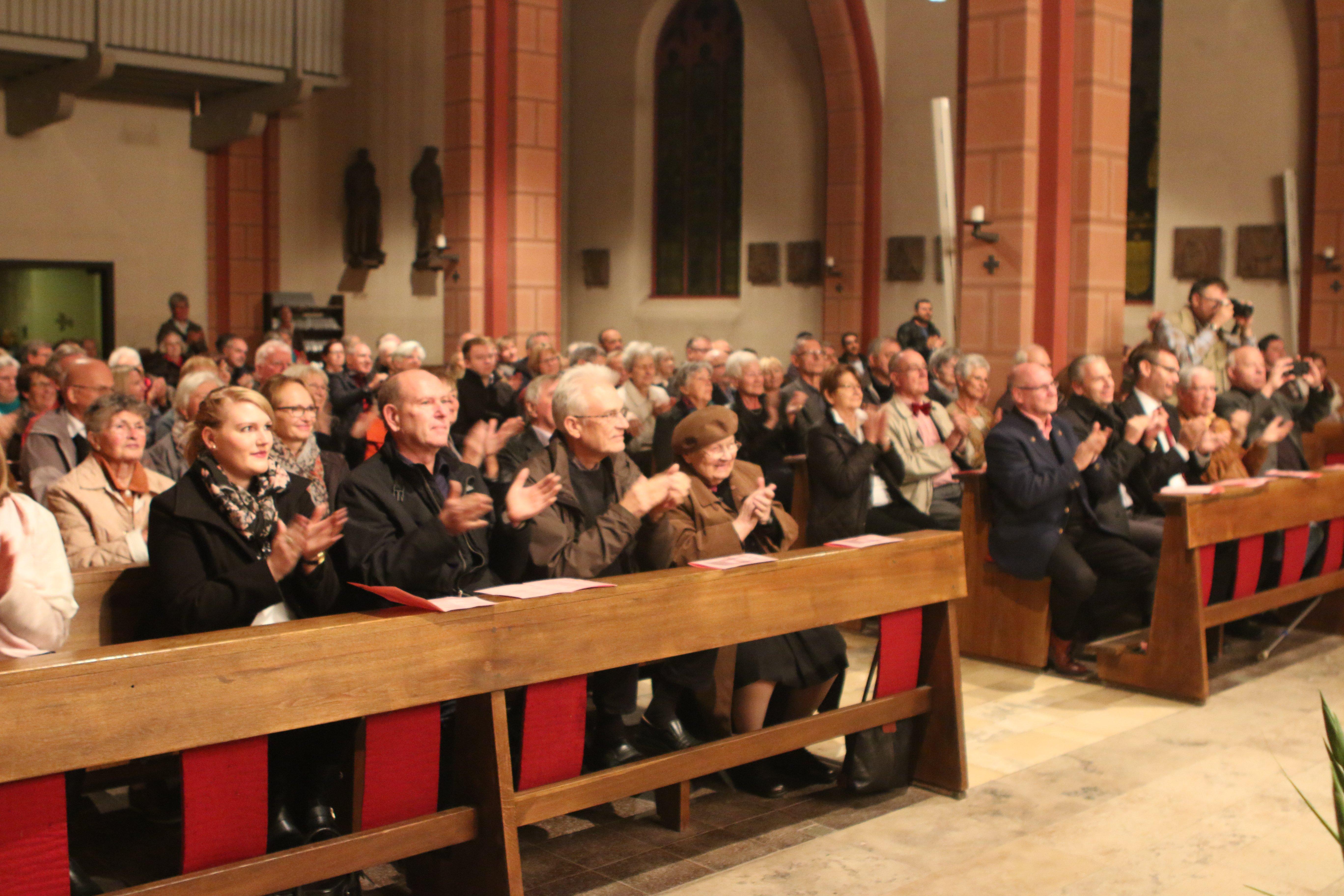 Blick von vorne auf applaudierende Besucher der katholischen Kirche während einer Veranstaltung im Innenraum